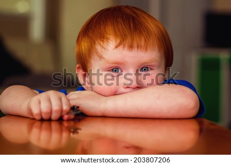 2 year old boy playing at a wooden table -- image taken indoors in Reno, Nevada, USA