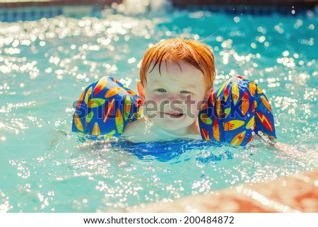 2 year old boy playing in the pool -- image taken outdoors in Reno, Nevada, USA