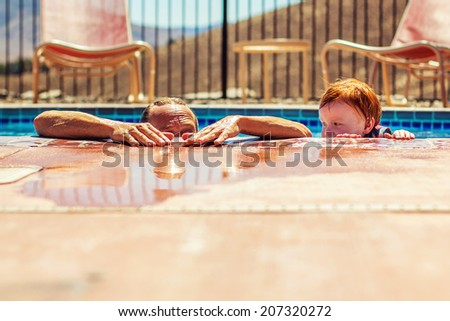 3 year old boy playing in the swimming pool with his grandfather, with his life jacket on -- image taken outdoors in Reno, Nevada, USA - stock photo