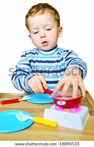 3-year-old boy playing with toy kitchen