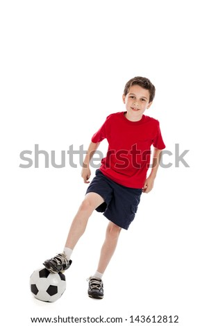 9 year old boy stepping on a soccer ball in the air isolated on white background