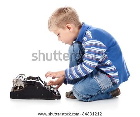 5 year old boy typing on old typewriter on white bacground - stock photo