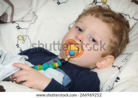 2-year-old boy with pacifier before falling asleep in bed - stock photo
