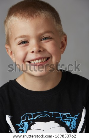 5 year old caucasian boy with short blonde hair, blue eyes and a light, healthy complexion wearing a long sleeve t-shirt. Shot in studio on a grey background. - stock photo
