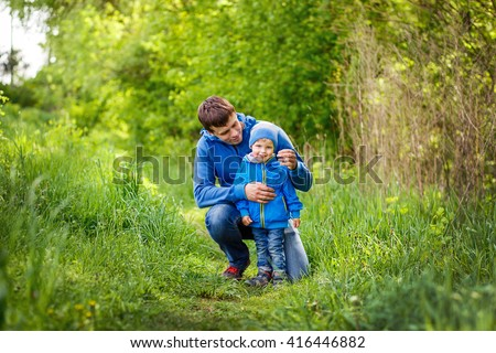 2-3-year-old cute boy dressed in a blue jacket and jeans staying with his father on the green grass in the park. Spring warm day. Around the beautiful nature. Trees and lush green grass. - stock photo