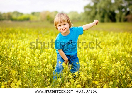 2-3-year-old cute boy having fun on the field with yellow flowers.