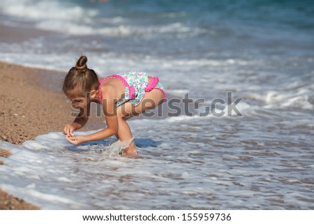 6 year old girl at the beach, searching for sea �¢??�¢??stones