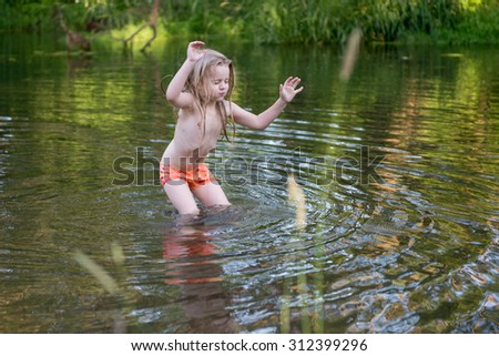 4 year old girl playing in a wild river - stock photo