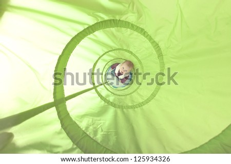 1 year old girl playing inside a toy tunnel. studio shot. - stock photo