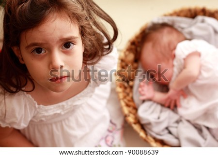 5-year-old girl with her newborn sister - stock photo