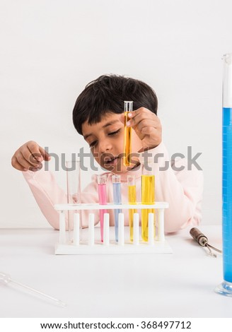 4 year old indian boy doing science experiment, science Education. asian kid and science experiments, chemistry experiment, indian boy and science experiments, indian kid and science lab  - stock photo