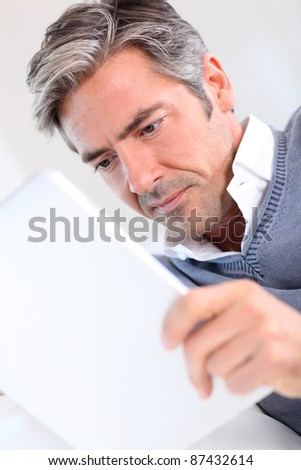 40-year-old man at home using electronic tablet - stock photo
