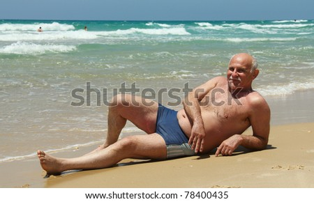 60-year-old man lying on the sand at the beach - stock photo