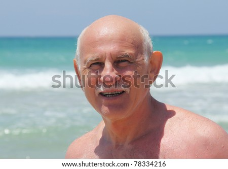60-year-old man resting on the beach - stock photo