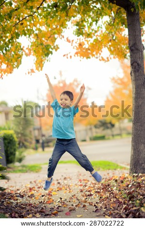 5 year old mixed race Asian Caucasian boy does a star jump (jumping jack) on the footpath (sidewalk) of his suburban neighborhood in Autumn (Fall) - stock photo