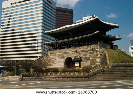 600 year old pagoda style Namdaemun City Gate in central Seoul with modern buildings.