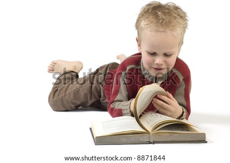 5 year old reading a book, isolated on white. Book is an old children's Bible.