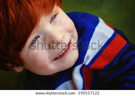 4 year old redheaded boy smiling while playing in a large green bin--image taken indoors using natural light (Sparks, Nevada, USA) - stock photo