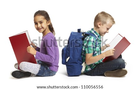 8 year old school boy and girl sitting reading with backpacks on white background - stock photo