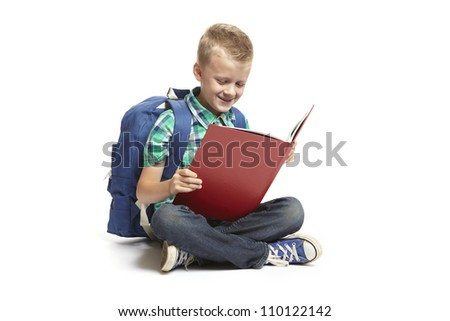 8 year old school boy sitting reading with backpack on white background
