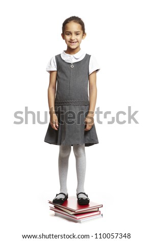 8 year old school girl stood on books smiling on white background