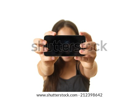 12 year old teenage girl taking a selfie / self portrait with her smartphone - isolated on white - stock photo