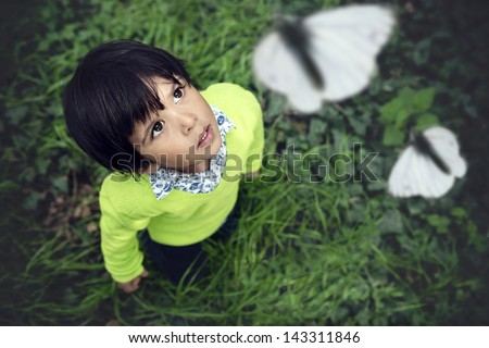 3 year old toddler looking up at white butterflies flying - stock photo
