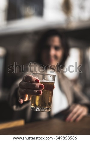 40 year old woman drinking beer on the terrace of a backlit bar