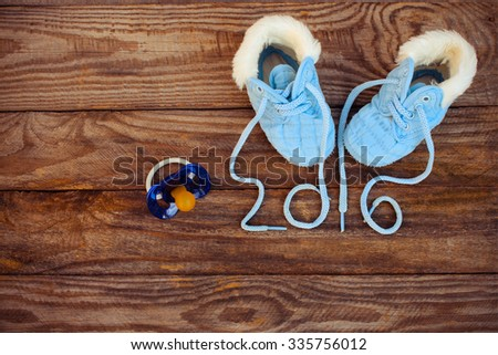 2016 year written laces of children's shoes and a pacifier on the old wooden background. Toned image  - stock photo