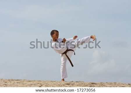 11-years boy doing Tae Kwon Do work-out on the Caribbean island beach. - stock photo