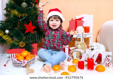 2 years boy in Santa hat sits near Christmas tree