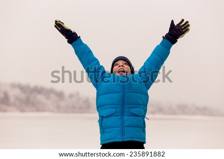 10-years boy jumping & screaming in the winter park. - stock photo