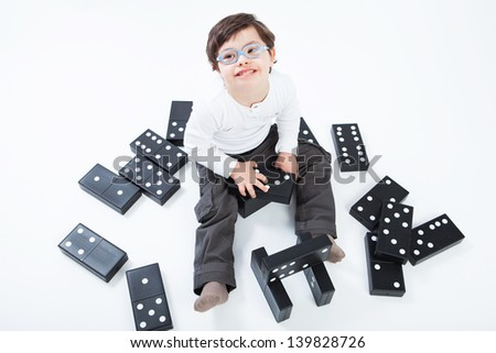 4 years boy with Down Syndrome playing with domino game on white background - stock photo