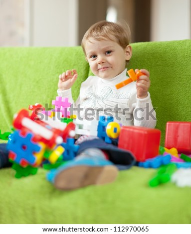 3 years child plays with toys in home interior