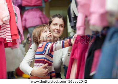 2 years child with mother chooses wear at clothes shop - stock photo