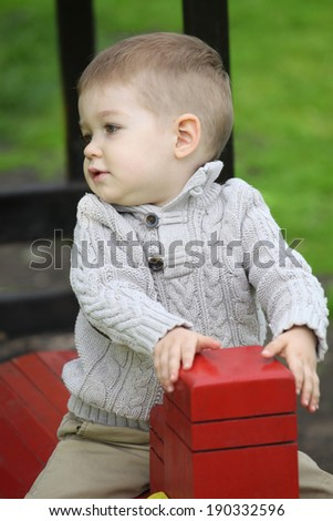 2 years old Baby boy on playground in spring outdoor park  - stock photo