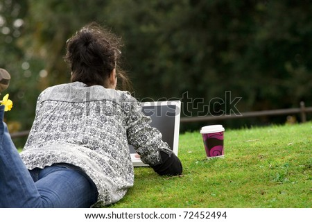 30-35 years old beautiful woman lying grass working on laptop computer in natural in  park - stock photo