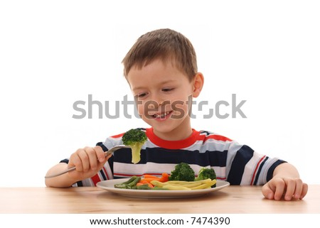 5-6 years old boy and plate of cooked vegetables isolated on white /focus on broccoli/ - stock photo