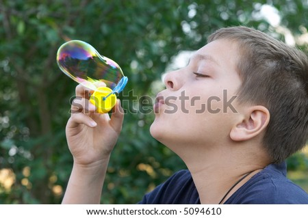 11 years old boy blowing soap bubbles outdoors