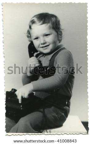 3-years-old boy calling by phone, posing in the studio; old photo taken in 1976 - stock photo