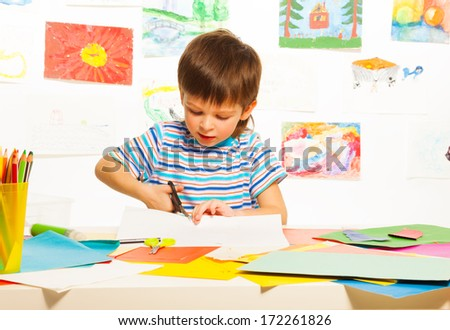 3 years old boy cutting cardboard paper with scissors in preschool art class  - stock photo