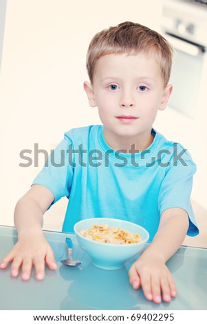 6 years old boy eating cereals - kids and family - stock photo