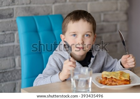 7 years old boy eating lasagne in dining room. Wears grey hoodie.
