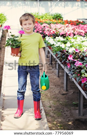 7 years old boy in his flower garden - kids and family - stock photo