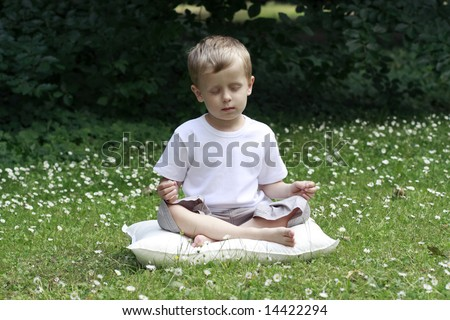 4-5 years old boy meditating outdoor - stock photo