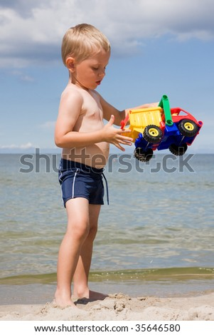 3 years old boy playing toy car on a beach - stock photo
