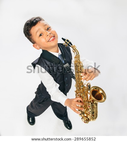 6 years old boy plays saxophone at studio. top view, looking at camera, wide angle,  - stock photo