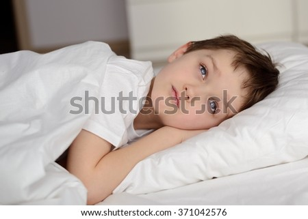 7 years old boy resting in white bed with eyes open. Sleeping boy. Sleeping child - stock photo