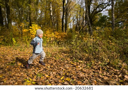 3 years old boy running fast in autumnal scenery - stock photo