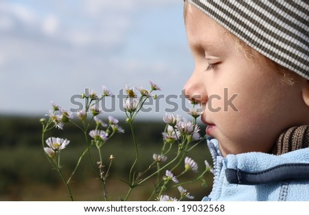 3 years old boy smelling autumnal flower outdoors - stock photo